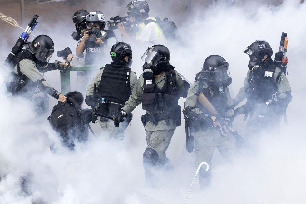 Agentes antidisturbios de Hong Kong entre el humo de sus botes