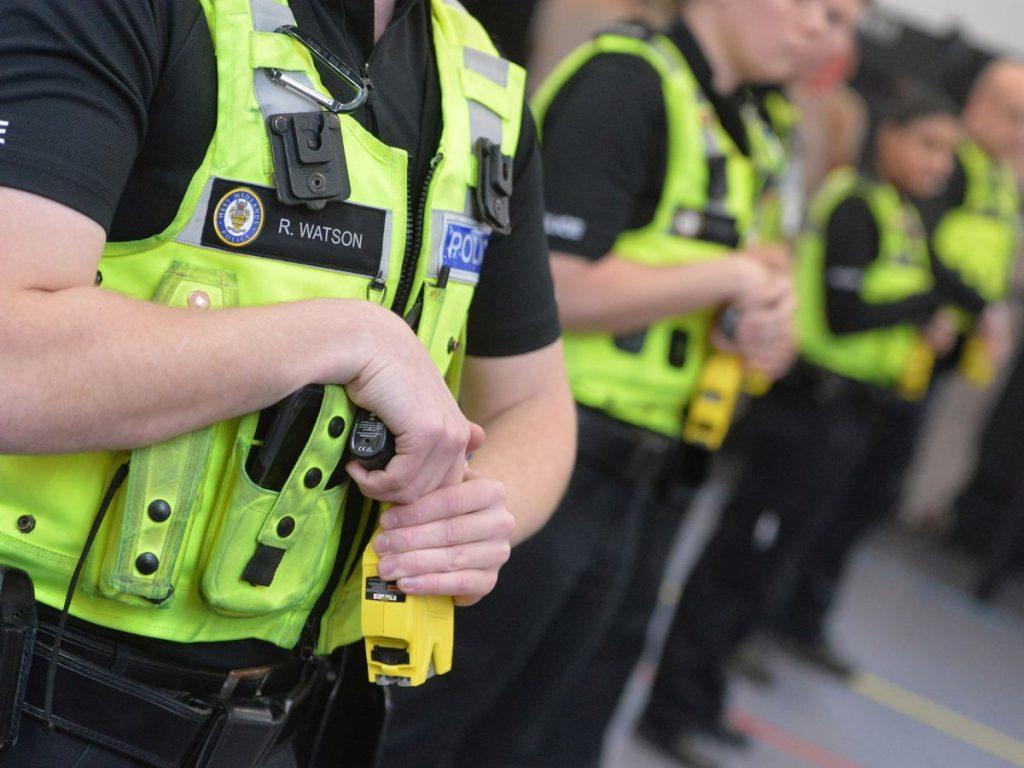 Agentes de policía posan con sus pistolas electricas Taser