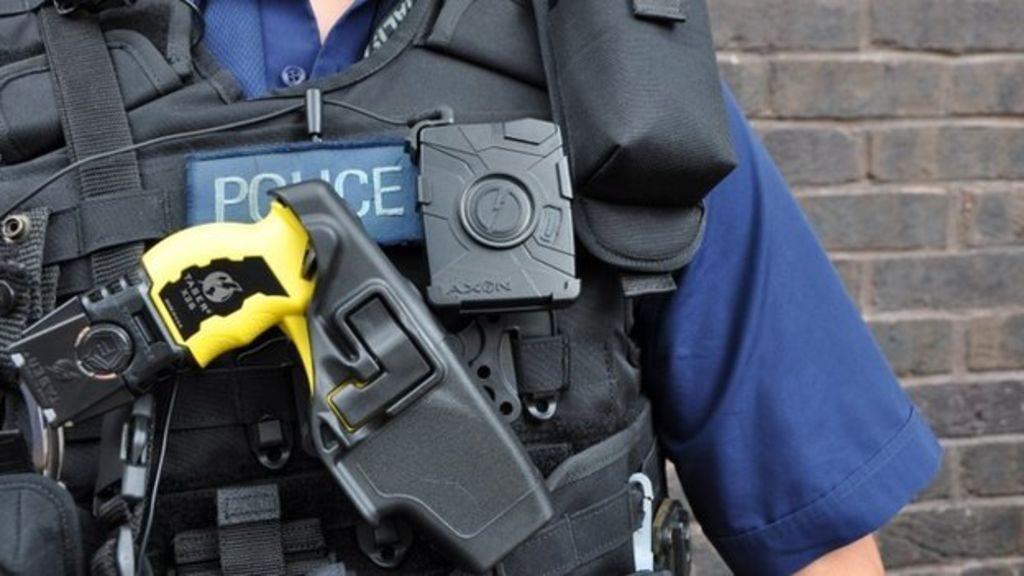 Agente de policia equipado con pistola taser y cámara personal Axon