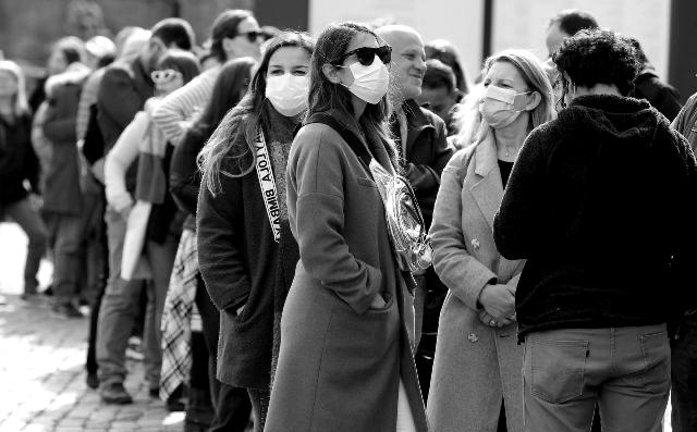 Grupo de personas espera protegidos con mascarillas contra el coronavirus