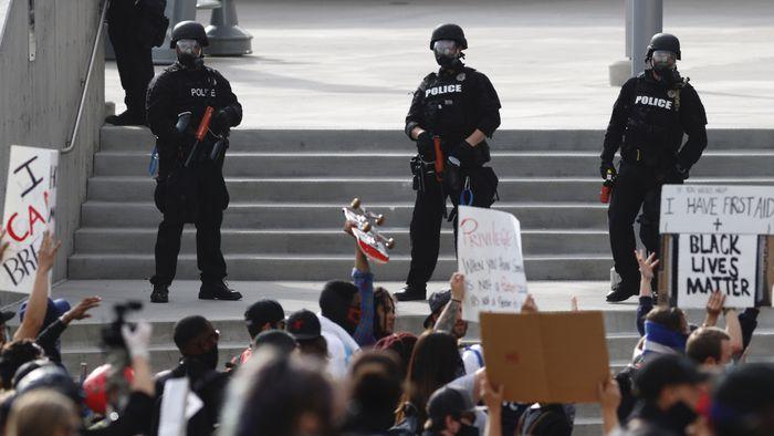 agentes de policia de estados unidos observan a los manifestantes