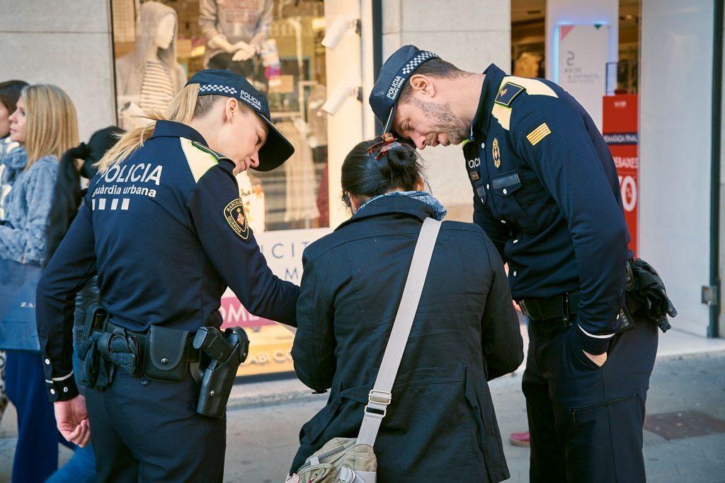 Dos agentes de guardia urbana atienden a una señora