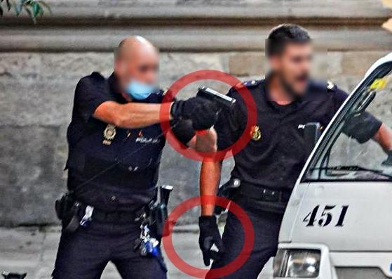 Dos policías nacionales apuntan su arma con guantes anticorte