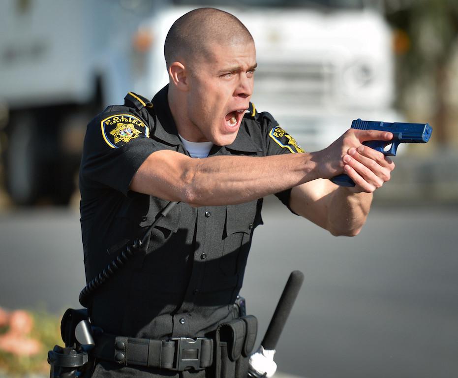 Agente de policía entrenando con su arma de plástico