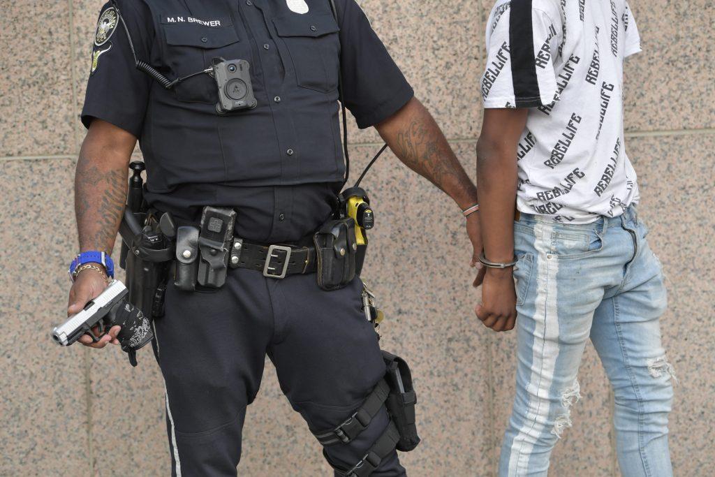 Policia mantiene esposado a delincuente al que ha desarmado mientras lo graba con su cámara individual en su pecho