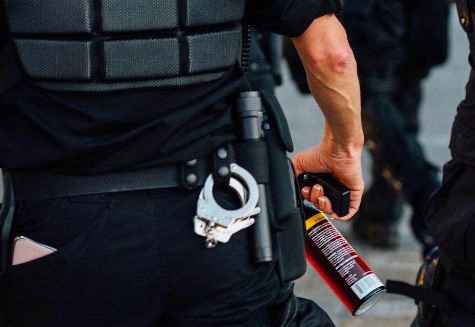 Policía con spray de pimienta para antidisturbios