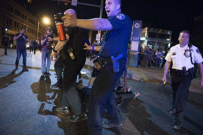 Agente con spray antidisturbios en su mano